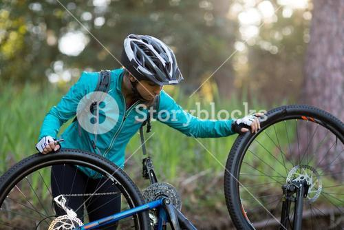 Female biker repairing mountain bike