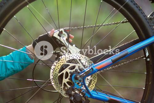 Hand of female biker repairing mountain bike