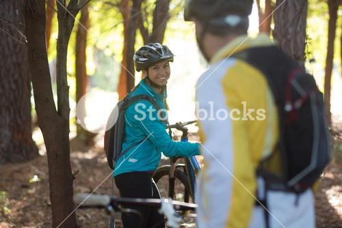 Biker couple interacting while standing with mountain bike