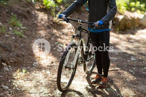 Female biker standing with mountain bike on dirt track