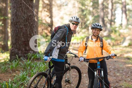 Biker couple standing with mountain bike on dirt track