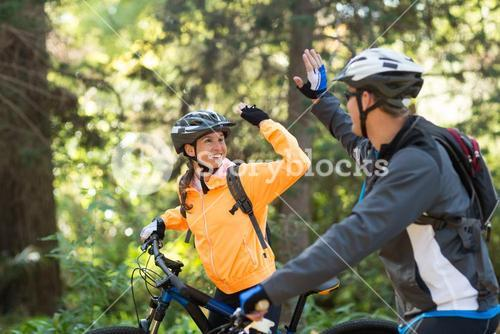 Biker couple giving high five while riding bicycle in the forest