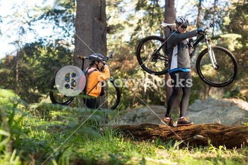 Biker couple holding their mountain bike and walking in forest
