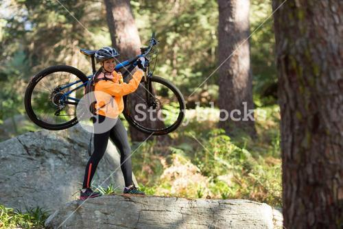 Female biker holding mountain bike and walking in forest
