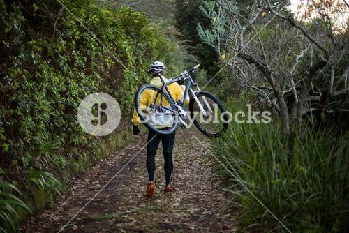 Male biker carrying mountain bike and walking on dirt track