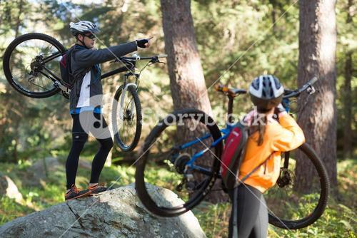 Biker couple holding their mountain bike and pointing at distance