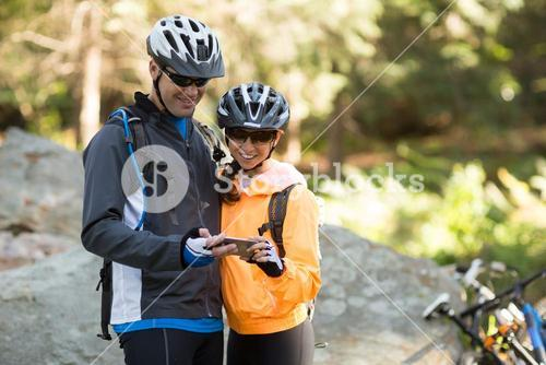 Biker couple using mobile phone in forest