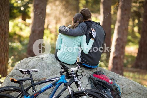Biker couple sitting on rock in forest