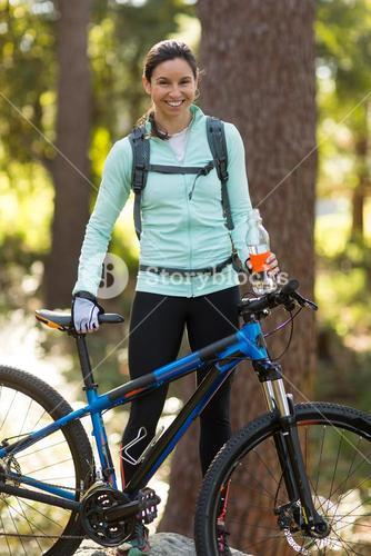 Female biker standing with mountain bike in forest