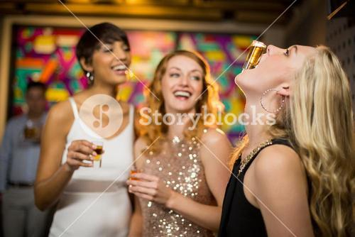 Woman balancing a shot glass on her mouth
