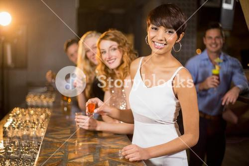 Group of friends having tequila in bar