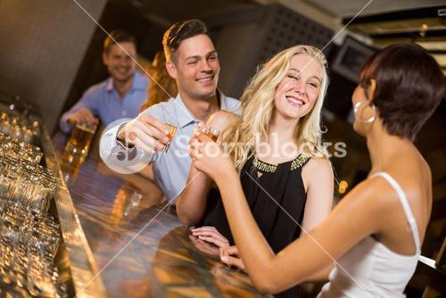 Group of friends toasting a glasses of tequila shot