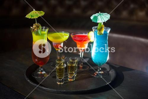 Various cocktail drinks and shot glasses of tequila on serving tray
