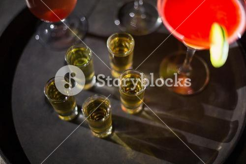 Cocktail drinks and shot glasses of tequila on serving tray