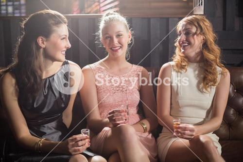 Three female friends holding shot glass of tequila in bar