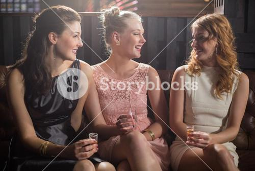 Three female friends interacting with each other while having tequila in bar