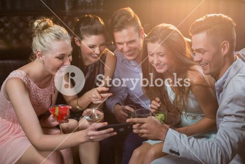 Smiling friends looking at mobile phone while having cocktail