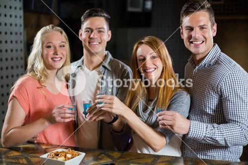 Group of friends standing at bar counter and having tequila shots