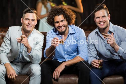 Three happy friends having cigar and whisky in bar