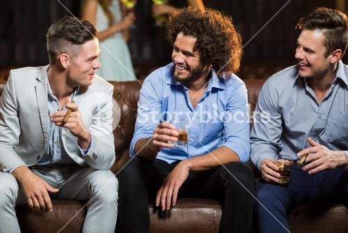Friends interacting with each other while having cigar and whisky in bar