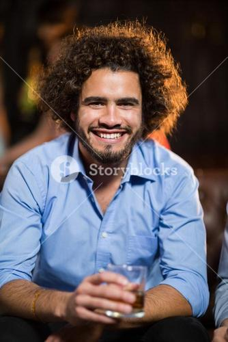 Smiling man holding glass of whisky in bar