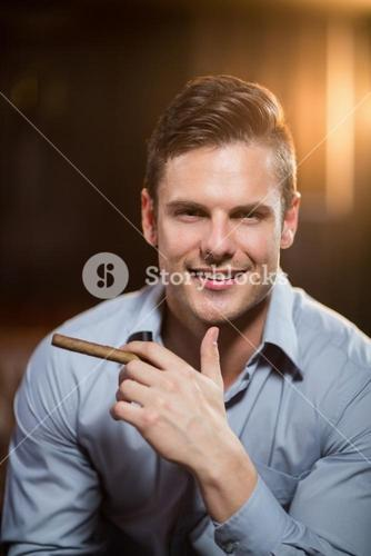 Smiling man holding a cigar in bar