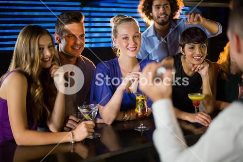 Happy friends standing at bar counter