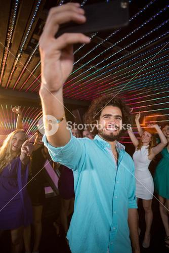 Man taking a selfie from mobile phone while friends dancing on dance floor
