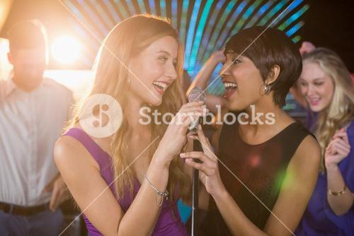 Two beautiful women singing song together