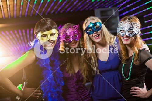 Female friends wearing masquerade in bar