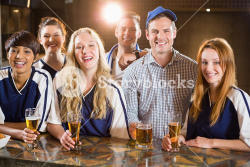 Group of friends having glass of beer in party