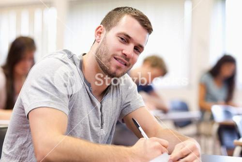 Smiling young adult writing