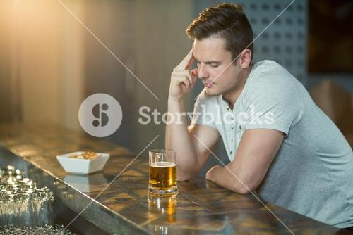 Thoughtful man with glass of whisky sitting at bar counter