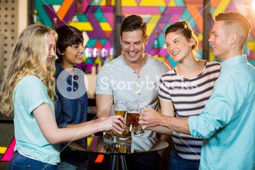 Group of friends toasting glass of beer in party