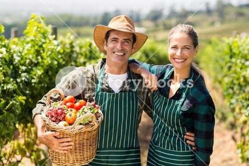 Portrait of happy farmer couple holding a basket of vegetables