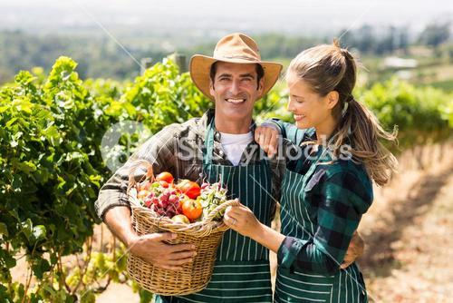 Happy farmer couple holding a basket of vegetables