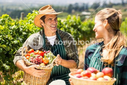 Happy farmer couple holding baskets of vegetables and fruits