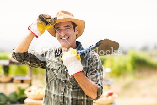 Portrait of farmer carrying shovel