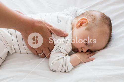 Mom putting baby to sleep in baby bed