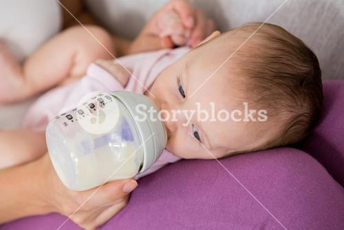 Mother feeding baby with milk bottle in living room