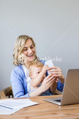 Mother and baby sitting at table and using mobile phone