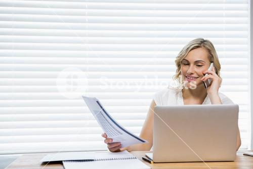 Beautiful woman talking on mobile phone while holding document