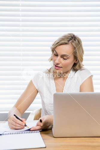 Beautiful woman writing on paper
