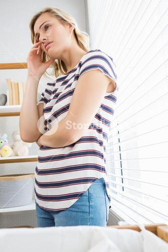 Depressed woman in deep thought standing near window