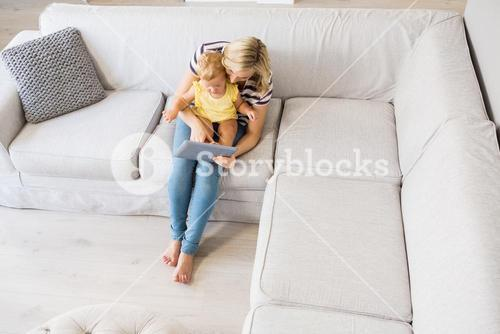 Mother and baby girl using digital tablet