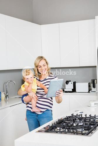 Mother and baby girl using digital tablet in kitchen