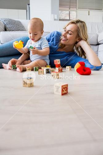 Mother looking at baby boy playing with toys in living room