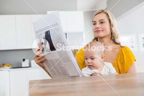 Mother reading newspaper with baby boy in kitchen