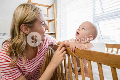 Mother playing with her baby boy in cradle
