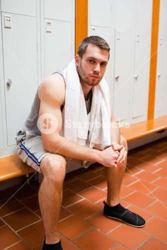 Portrait of a young sports student sitting on a bench